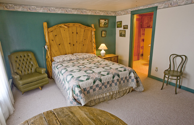 A second queen room with attached bathroom and comfortable green chair.